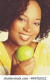 Beautiful smiling black woman holding green apple