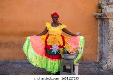 Eine schöne, lächelnde Schwarze, die traditionelle Kostüme trägt, verkauft Obst im Zentrum von Cartagena.