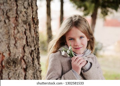 Beautiful smiling blond little girl with bouquet of first spring flowers snowdrops. Girl holds flowers and smiling to camera
