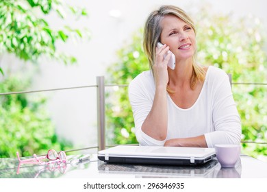 beautiful smiling blond woman talking on the phone