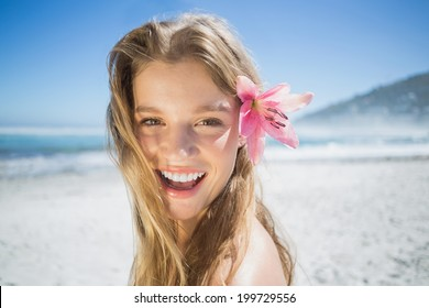 Beautiful smiling blonde with flower hair accessory on the beach on a sunny day