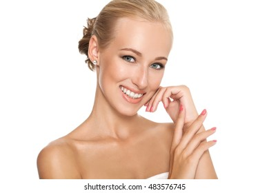 Beautiful smiling blonde girl with clean skin, natural make-up, and white teeth on background. Beautiful woman with bare shoulders. Hand near the face.
