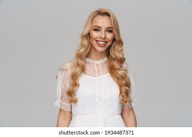 Beautiful smiling blonde haired young woman in dress standing isolated over blue background, posing