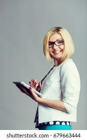 Beautiful smiling blonde holding smartphone