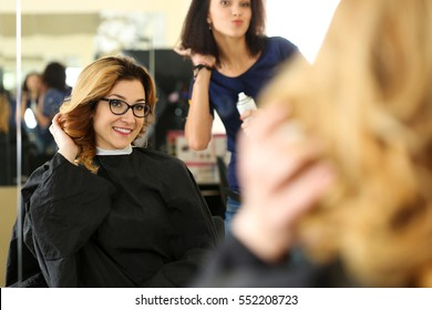 Beautiful smiling blonde woman at hairdresser checking and fixing new curly hairdo with hand. Keratin restoration, latest trend, fresh idea, haircut picking, shorten tips, instrument store concept