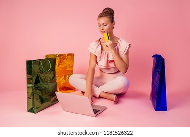 beautiful smiling blonde woman shopaholic bag and credit card in her hand pink background in studio . concept of seasonal black friday sale and online shopping