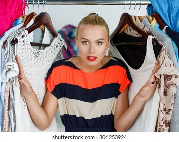 Beautiful smiling blonde woman standing inside wardrobe rack full of clothes suffering with choice. Shopping and consumerism or stylist concept. Nothing to wear and hard to decide concept
