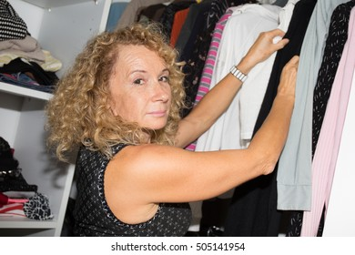 Beautiful smiling blonde woman standing inside wardrobe rack full of clothes