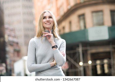 Beautiful smiling blonde woman thinking and walking on city street