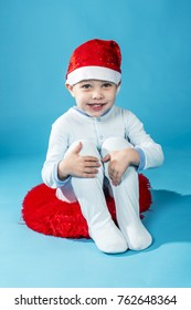 beautiful smiling boy in pajamas and a Santa Claus hat sits on a red pillow on a blue background