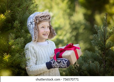 beautiful smiling boy in trapper hat and mittens holding christmas gift standing by the tree, winter holiday concept