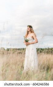 Beautiful smiling bride wearing a natural flower wreath and standing in the golden summer fields with eucalyptus in hands.