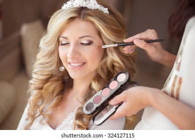 Beautiful smiling bride wedding portrait with makeup and hairstyle. Stylist makes make-up girl on wedding day. portrait of young woman at morning.