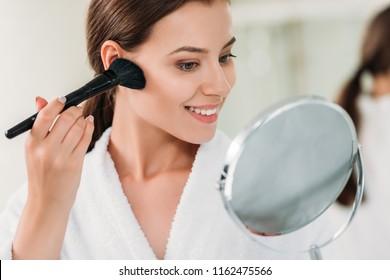 beautiful smiling brunette girl in bathrobe applying powder bronzer with brush