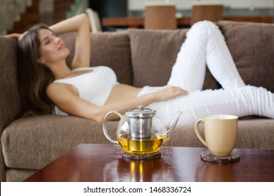 beautiful smiling brunette girl dressed in white jeans and top lying relaxed on sofa. glass teapot with tea and mug on the table in foreground. focus on pot and cup