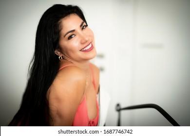 Beautiful smiling brunette girl with long black hair posing