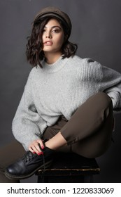 Beautiful smiling brunette girl wearing a casual style sweater, pants, cap and a boots sits with her leg up on a stool on a gray background. Natural makeup. Fashion and commercial design. Copy space.