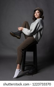 Beautiful smiling brunette girl wearing a casual style sweater, pants and cap puts a shoe on her leg on a gray background. Natural nude makeup. Fashion, advertising and commercial design. Copy space.