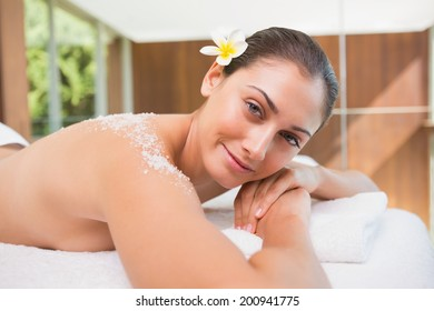 Beautiful smiling brunette lying on massage table with salt scrub on back in the health spa