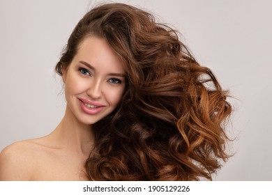 Beautiful smiling brunette woman with luxurious curly brown hair. Copycpase