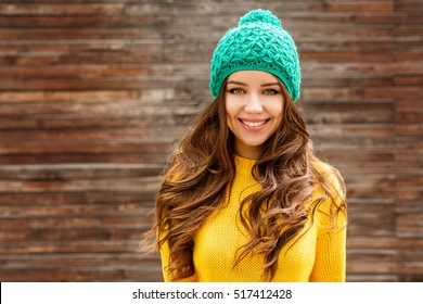 Beautiful smiling brunette woman with luxurious hair over wooden background. Autumn time. Fall season.