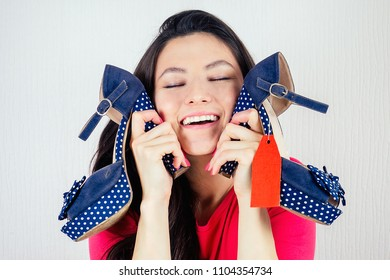 beautiful smiling brunette woman shopaholic holding a stylish shoes with a red label ( tag , tab , tally ) in her hand . concept of seasonal sales and shopping