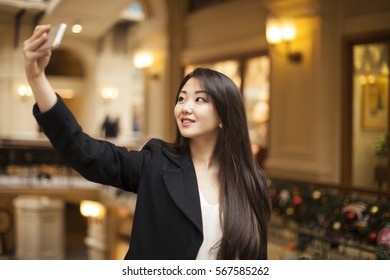 Beautiful, smiling brunette woman take a picture of herself with a smartphone. selfie