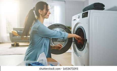 Beautiful Smiling Brunette Young Woman Sits in Front of a Washing Machine in Homely Jeans Clothes. She Loads the Washer with Dirty Laundry. Bright and Spacious Living Room with Modern Interior.