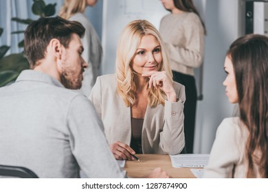 beautiful smiling business mentor sitting with hand on chin and looking at young colleagues in office