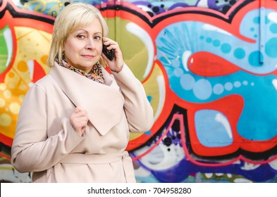 Beautiful smiling business older woman in a light beige coat talking on a mobile phone on the graffiti background