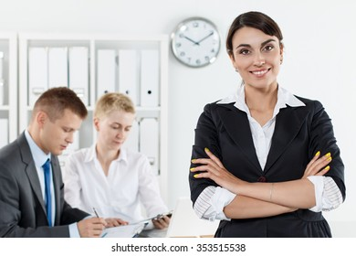 Beautiful smiling business woman in suit standing with hands crossed on chest while couple employees working in background. Serious business and partnership, job offer, financial success concept
