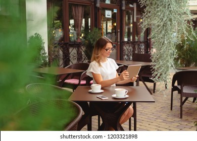 Beautiful smiling caucasian business woman using digital tablet and drinking coffee in a cafe.