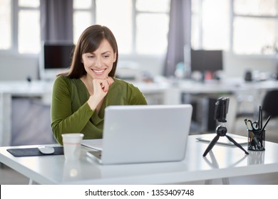 Beautiful smiling Caucasian businesswoman sitting in modern office and using laptop.