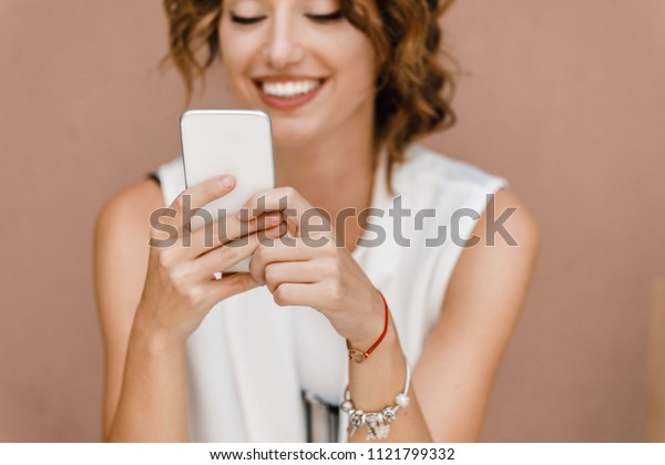 Beautiful smiling Caucasian woman typing on her mobile phone.