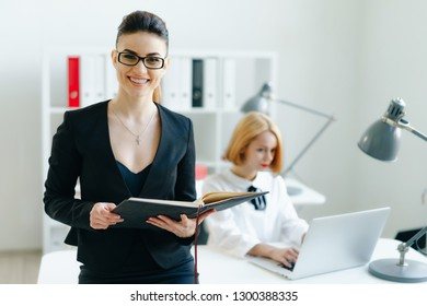 Beautiful smiling cheerful girl at workplace look in camera with colleagues group in background. White collar worker at workspace job offer modern lifestyle client visit profession train concept