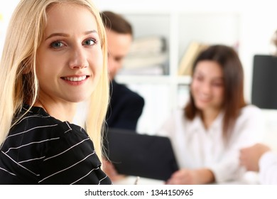 Beautiful smiling cheerful girl at workplace look in camera with colleagues group in background concept.