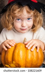 Beautiful smiling child in pointed hat of witch holding a big orange pumpkin. Halloween concept