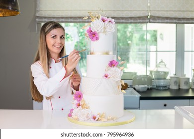 Beautiful smiling confident confectioner in chefs uniform standing in the modern kitchen, holding a brush and gold paint, decorating a four tier white, pink and gold wedding cake
