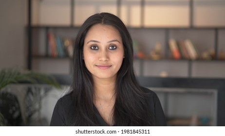 Beautiful smiling confident young Indian ethnic woman pretty face looking at camera posing alone at home in office, happy millennial Hindu ethnicity girl student professional close up front portrait.