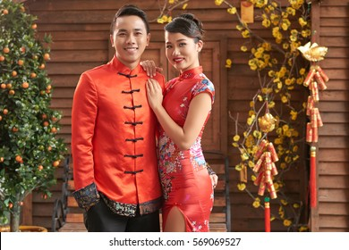 Beautiful smiling couple in Chinese national costumes ready to celebrate Lunar New Year