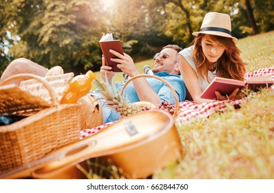 Beautiful smiling couple enjoying in good books and picnic day in the park. Love and tenderness, dating, romance. Lifestyle concept