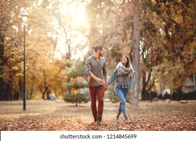 Beautiful smiling couple enjoying in sunny city park in autumn colors looking each other.