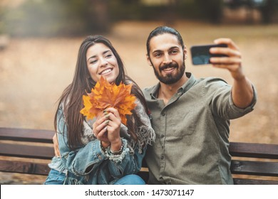 Beautiful smiling couple is enjoying in sunny city park in autumn colors. They are sitting on the bench and having fun with smarthphone taking selfie.