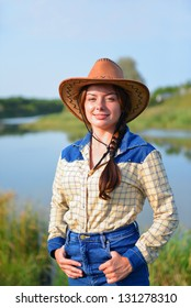 Beautiful Smiling Cowgirl front of lake