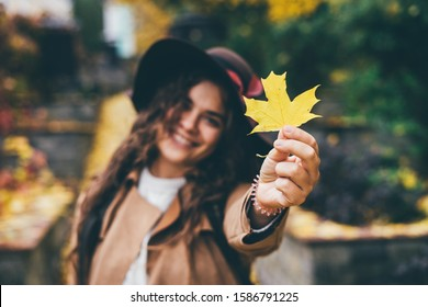 A beautiful smiling curly young girl in a brown hat with wide brim and a beige coat shows yellow maple leaf in frame. Stands in the autumn park. Focus on the yellow maple leaf.