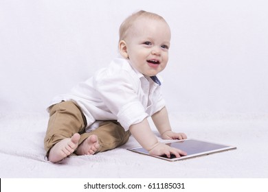 Beautiful smiling cute baby with a tablet. Adorable infant boy playing with a tablet