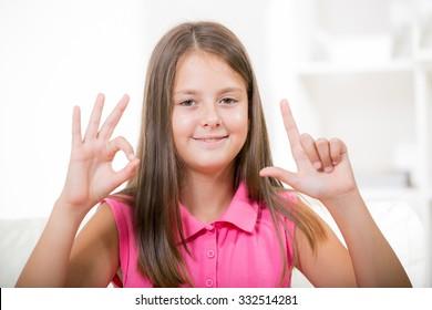 Beautiful smiling deaf girl using sign language