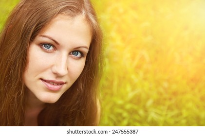 beautiful smiling dreaming woman in a summer park on a background of green grass