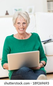 Beautiful smiling elderly woman sitting on the floor at home leaning against the sofa with her laptop balanced on her knees looking at the camera with a smile
