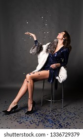 Beautiful, smiling, elegant brunette woman, dressed in a brilliant blue dress and fur coat, sits on a chair and throws festive glitter and confetti into the air and blows on it. Gray background.